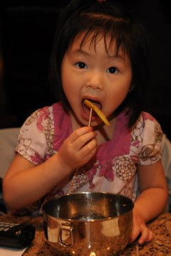 Elina Lindberg, 3, eats quick pickled Chayote squash Saturday night.  She contined to eat though the spice from the chili made her suck in air to cool off her tongue.