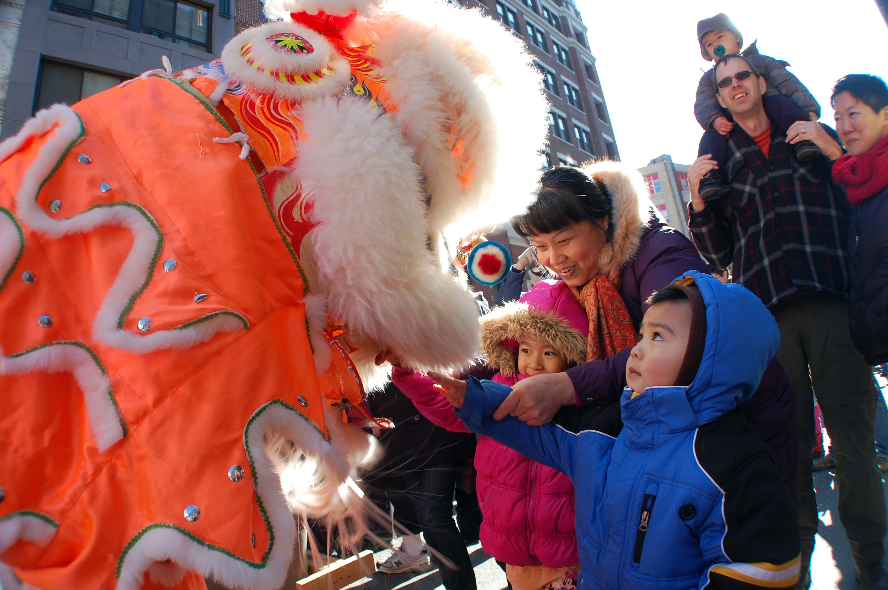 Children going up to touch the lion after his dance