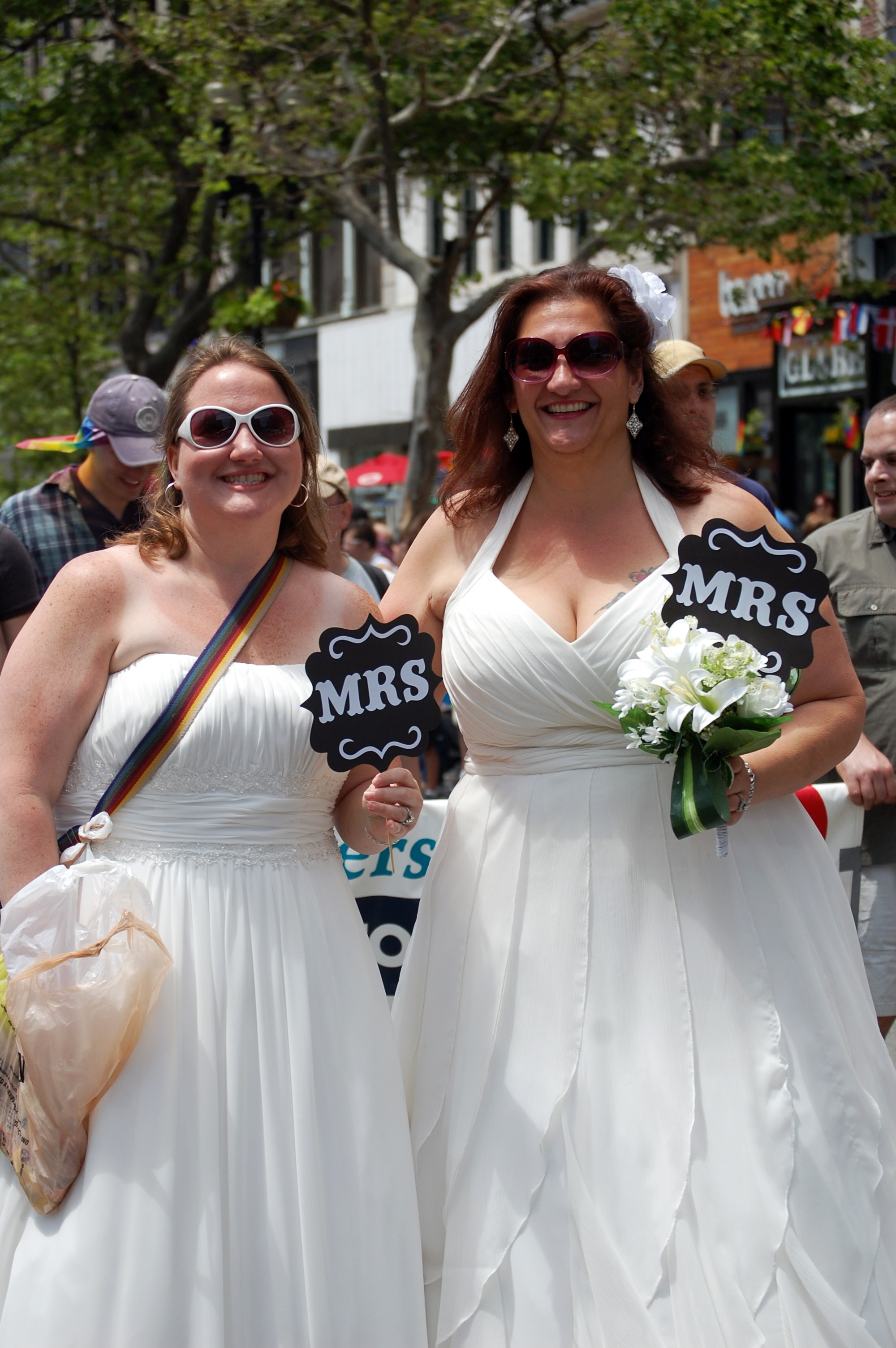 A newlywed couple marches in the Boston Pride Parade in their wedding gowns.