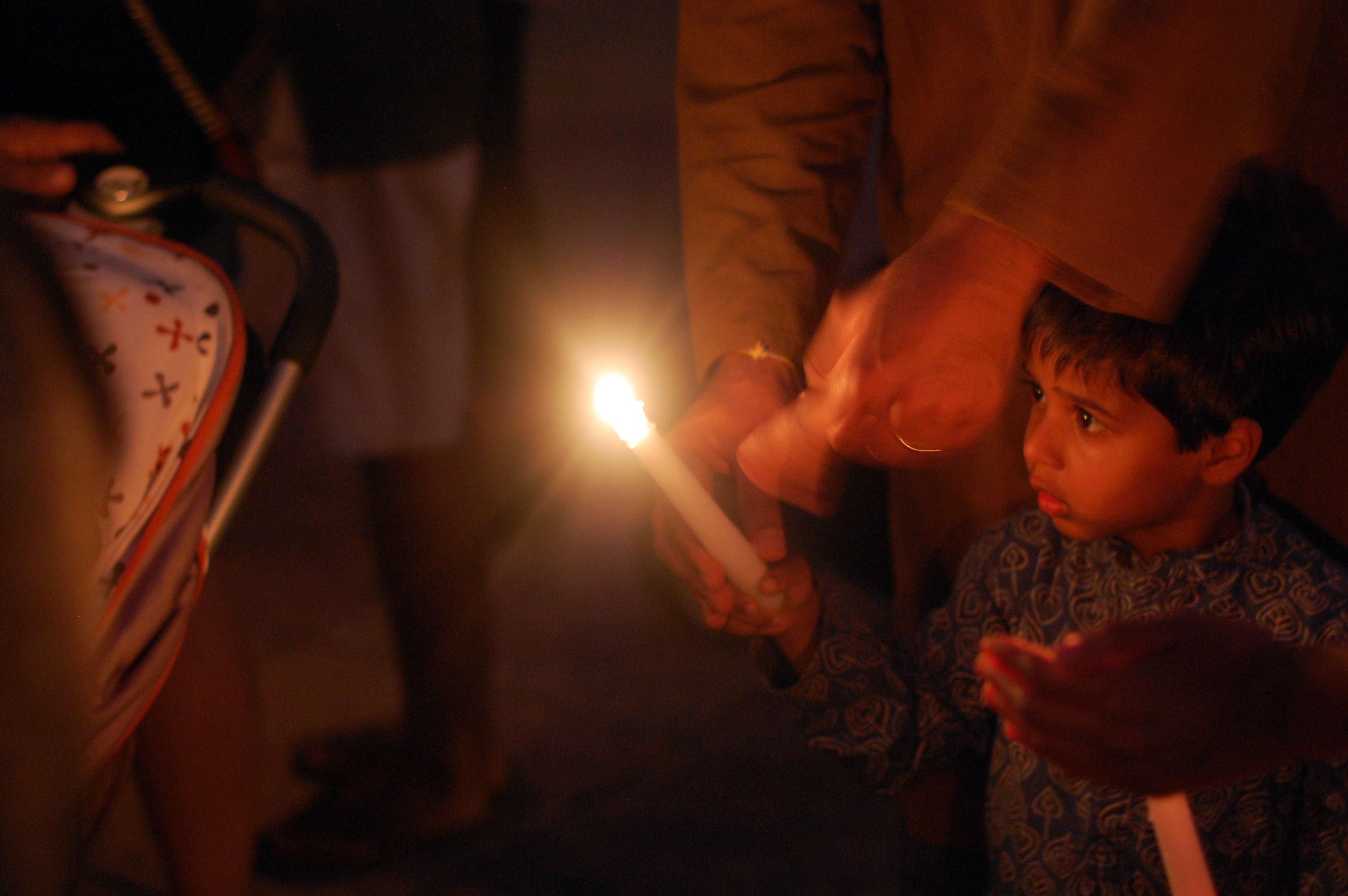 A father helps light his son's candle during the vigil