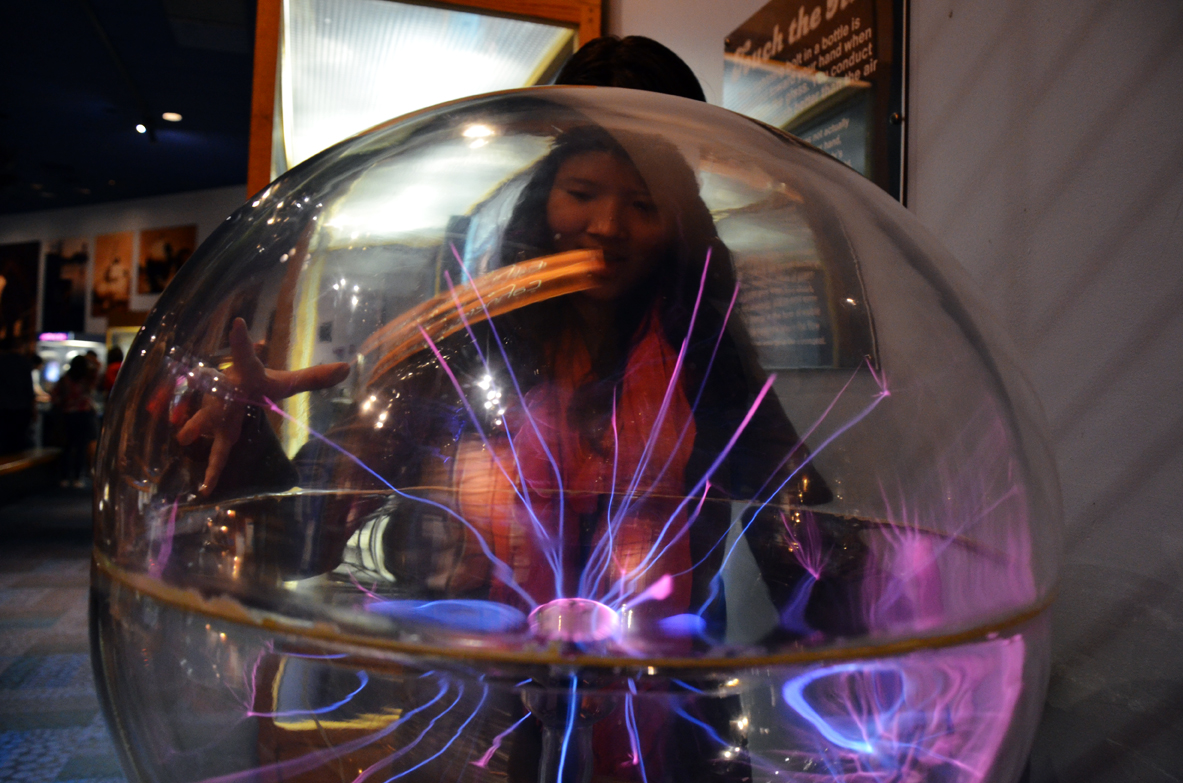 Student plays with electricity ball in the Museum's 'Lightning!' Exhibit - Photo by Kara Korab