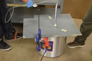After it's mixed, the mixture is put into a big pot. Here the hose coming out of the metal plate is connected to a vacuum, and the orange handle belongs to a drill that is clamped onto the sheet to shake out air bubbles. Photo by Jake Lucas
