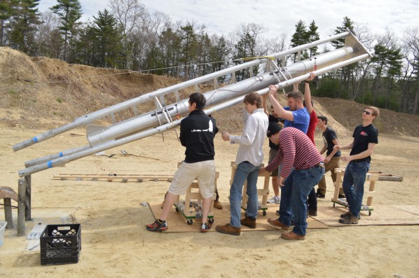 Members of the rocket propulsion group hoist the rocket onto its test stand. Photo by Jake Lucas.