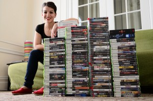 Anita Sarkeesian posing with some of the games that are used as examples in her series Tropes vs. Women. Photo credit to Anita Sarkeesian.