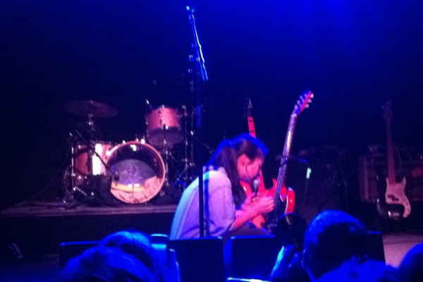 """Mitski unorthodoxly strumming her guitar in its stand while wrenching hearts during """"Class of 2013."""""""