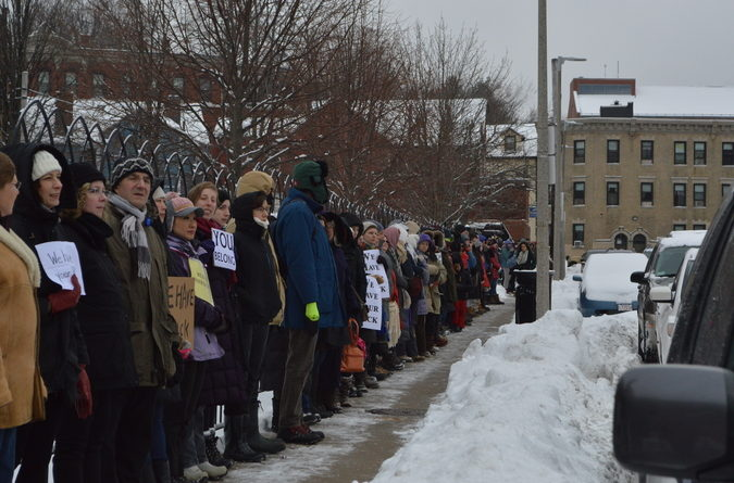 Approximately 65 people surround Islamic Society of Boston Cultural Center.