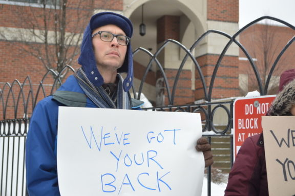 Protesters braved the snow and cold to stand for half an hour, silently holding their signs.