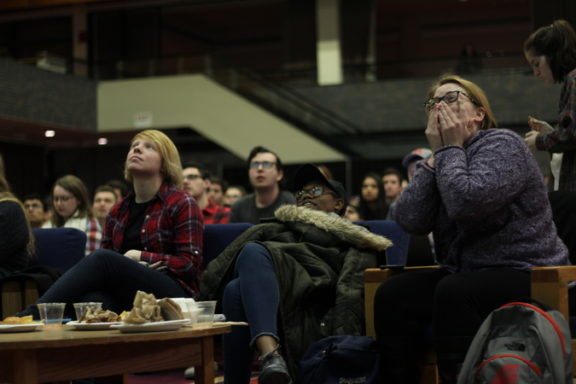 Students watch nervously as TV announcers discuss how hard it will be for the Pats to win.